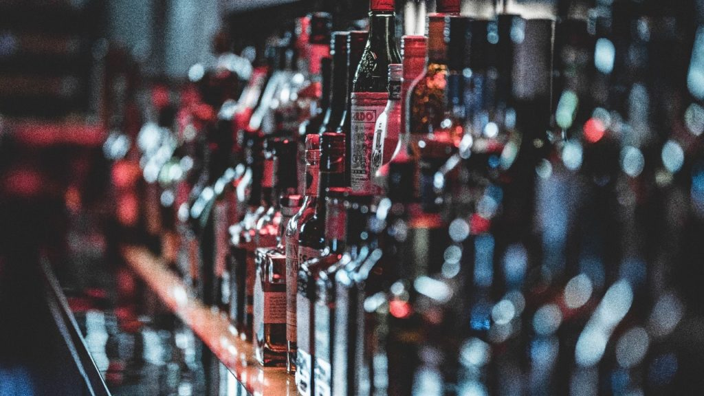 A row of alcohol bottles on a bar.