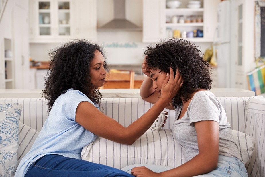 An African-American mother and daughter talking on the couch.