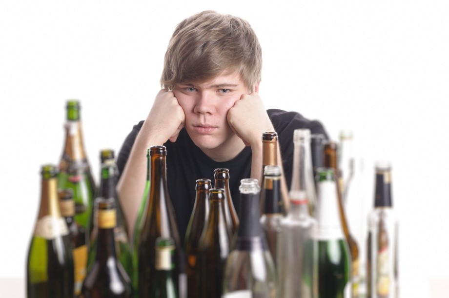 A sad teenage boy sitting in front of bottles of alcohol.