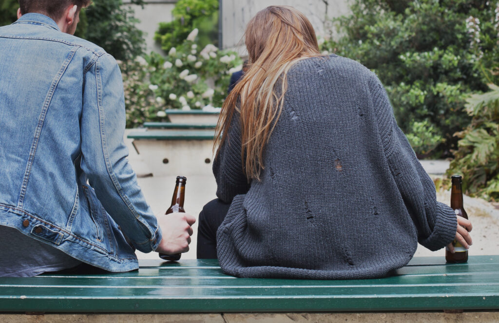 A teenage boy and teenage girl sitting on a bench drinking alcohol underage.