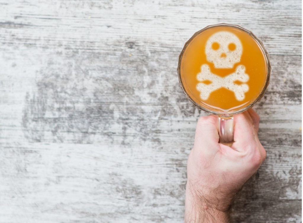 Glass of alcohol with skull and crossbones.